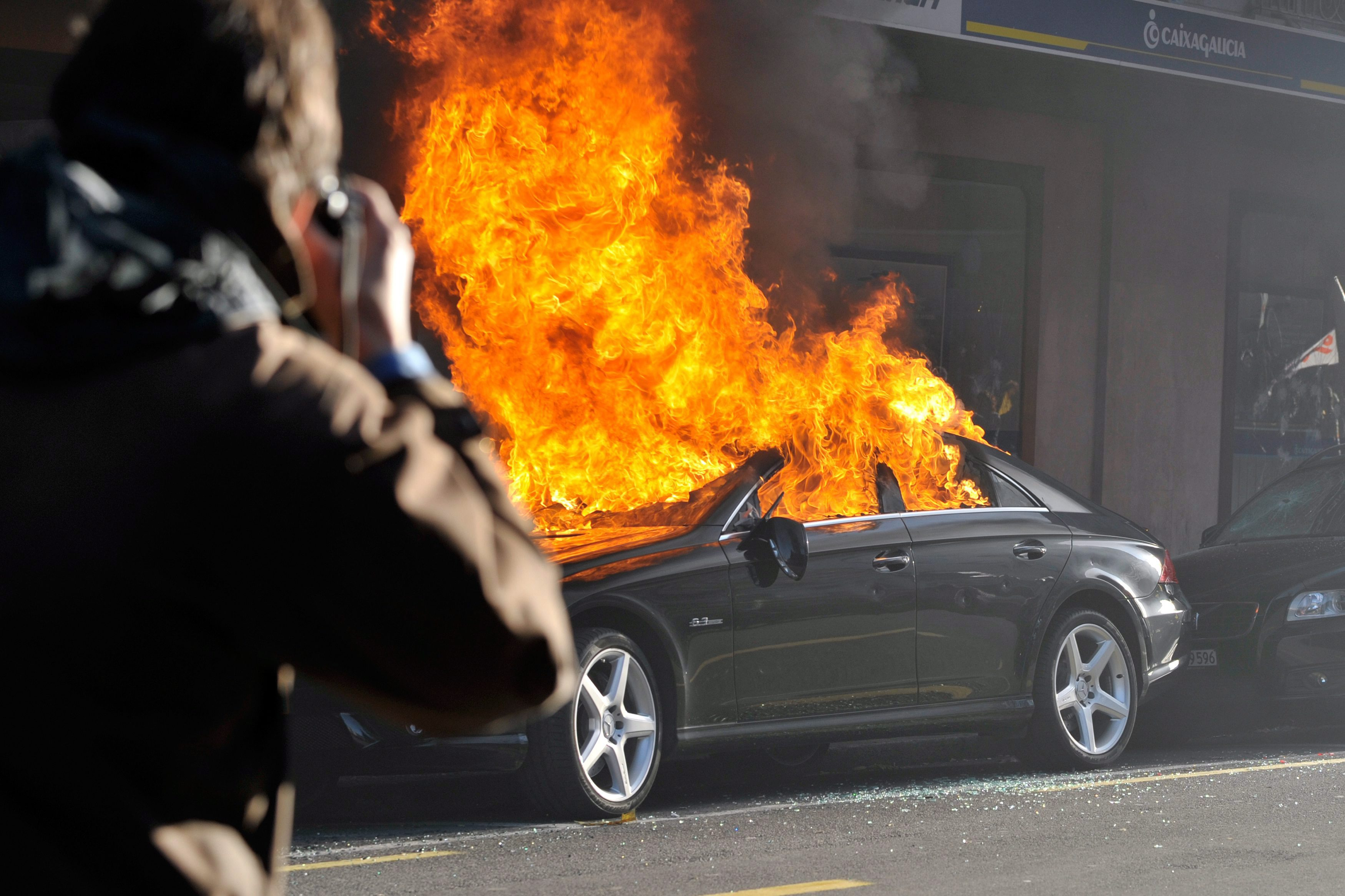 Cars have been set on fire by demonstrators during a protest against the seventh WTO Ministerial Conference